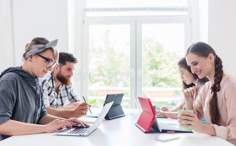 Gente joven dedicada que comparte un escritorio mientras que trabaja a distancia fotografía de archivo libre de regalías