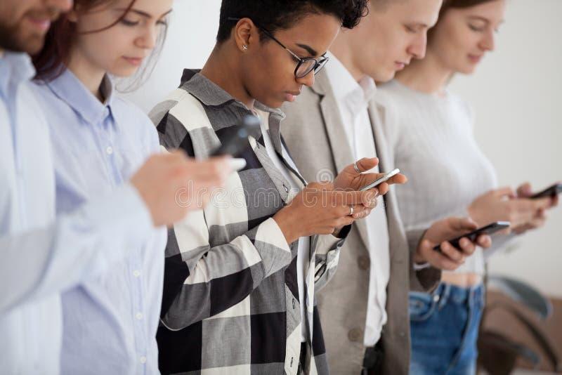 Gente joven diversa que se coloca en fila usando smartphones imagen de archivo