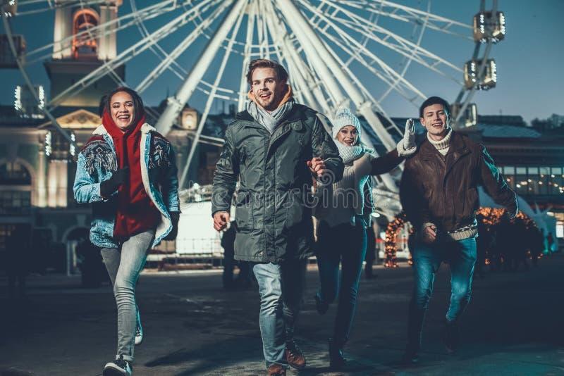 Gente joven emocional que corre al aire libre y que sonríe fotografía de archivo