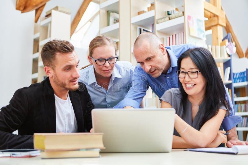 Gente joven en el ordenador portátil como equipo de lanzamiento imágenes de archivo libres de regalías