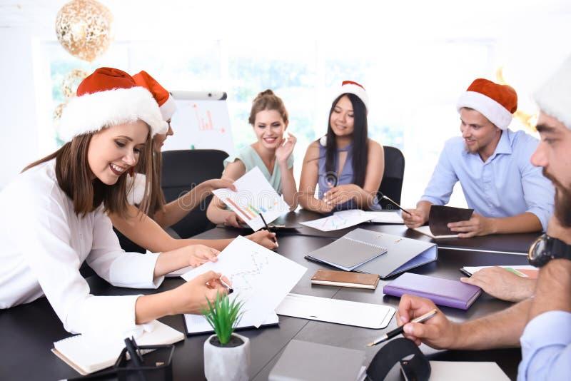 Gente joven en los sombreros de Papá Noel que trabajan en oficina imagen de archivo