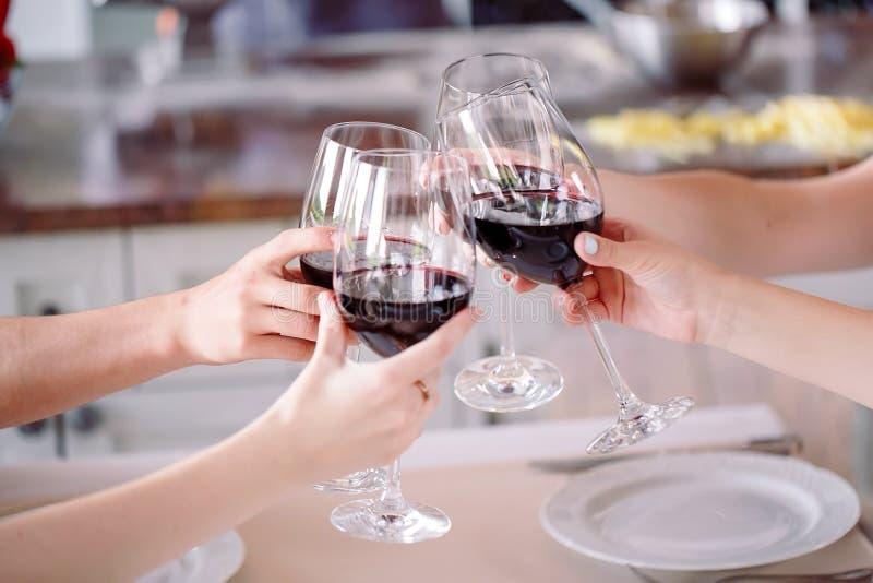 Gente joven en un vino de consumici?n del restaurante en el fondo que un cocinero se prepara fotografía de archivo