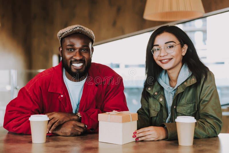 Gente joven encantada que siente feliz mientras que se sienta con poco presente imagenes de archivo