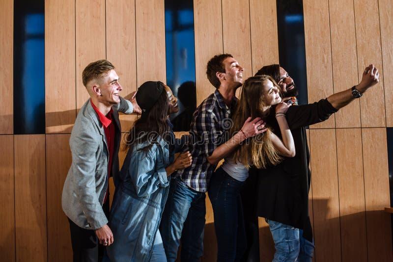 Gente joven feliz que hace el selfie en el cuarto cerca de la pared de madera fotos de archivo