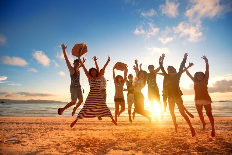 Gente joven feliz que salta en la playa en puesta del sol hermosa fotos de archivo