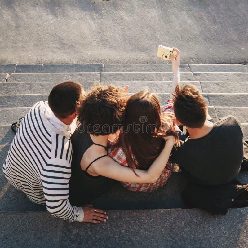 Gente joven feliz que toma el selfie en la cámara en ciudad foto de archivo