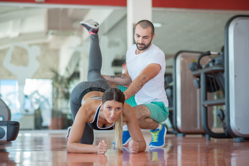 Gente joven implicada en deportes Mujer que estira con el instructor personal fotos de archivo