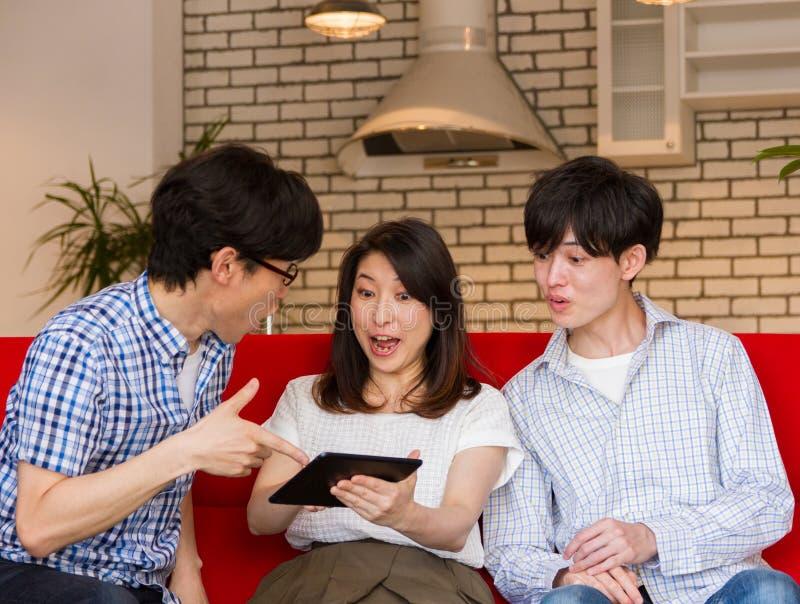 Gente joven japonesa que la observación contenta en Internet con el dispositivo de la tableta, hablando y riendo fotografía de archivo