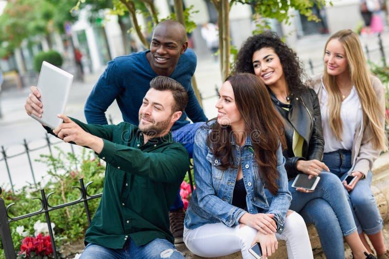 gente joven Multi-étnica que toma el selfie junto en fondo urbano foto de archivo libre de regalías