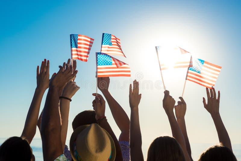 Gente joven que agita banderas americanas en la puesta del sol imagen de archivo libre de regalías