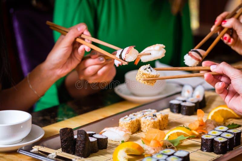 Gente joven que come el sushi en restaurante imagen de archivo