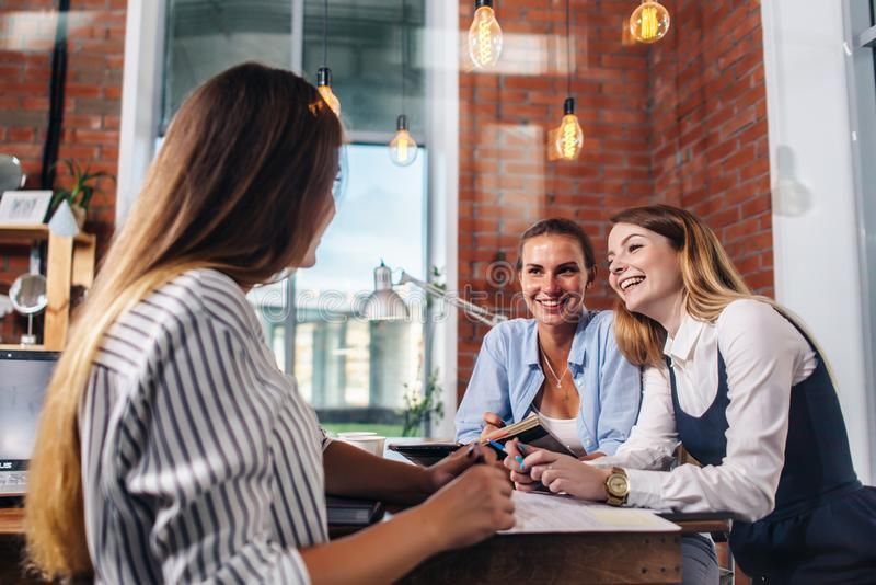 Gente joven que discute algo con la sonrisa que se sienta en la tabla de la oficina foto de archivo libre de regalías