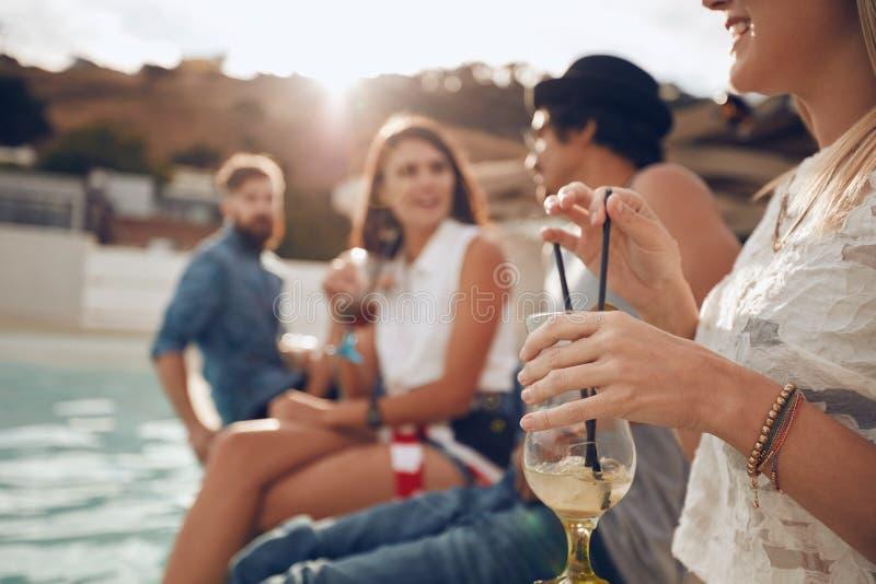 Gente joven que disfruta de un partido del poolside del cóctel imagen de archivo