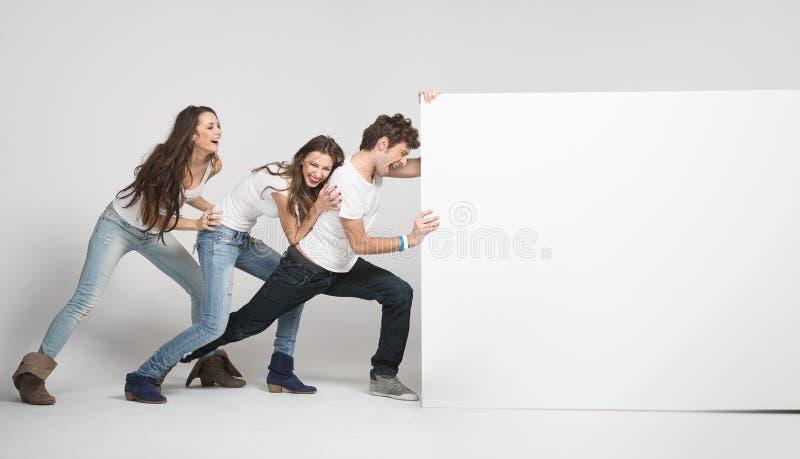 Gente joven que empuja a la tarjeta blanca fotos de archivo libres de regalías