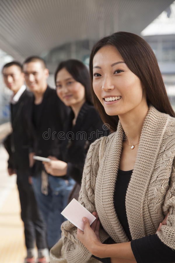 Gente joven que espera un tren en la plataforma imagenes de archivo