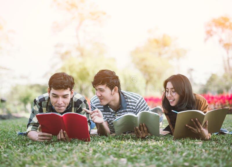 Gente joven que estudia el libro de lectura en parque estudio de la educación por leído fotos de archivo