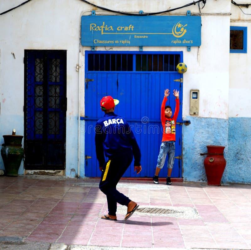Gente joven que juega a fútbol en el Medina de Essaouira imagen de archivo