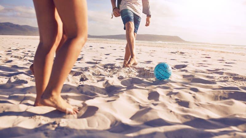 Gente joven que juega a fútbol en la playa fotos de archivo libres de regalías