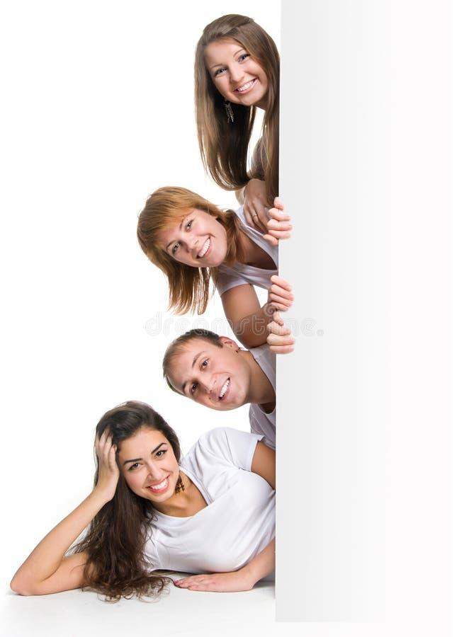 Gente joven que mira hacia fuera a una tarjeta foto de archivo libre de regalías