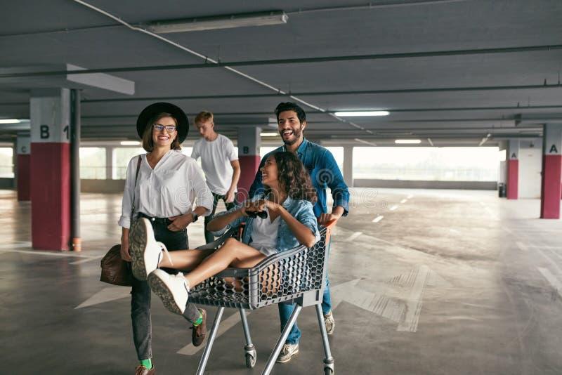 Gente joven que se divierte, compitiendo con en la carretilla que hace compras en el aparcamiento imagen de archivo libre de regalías