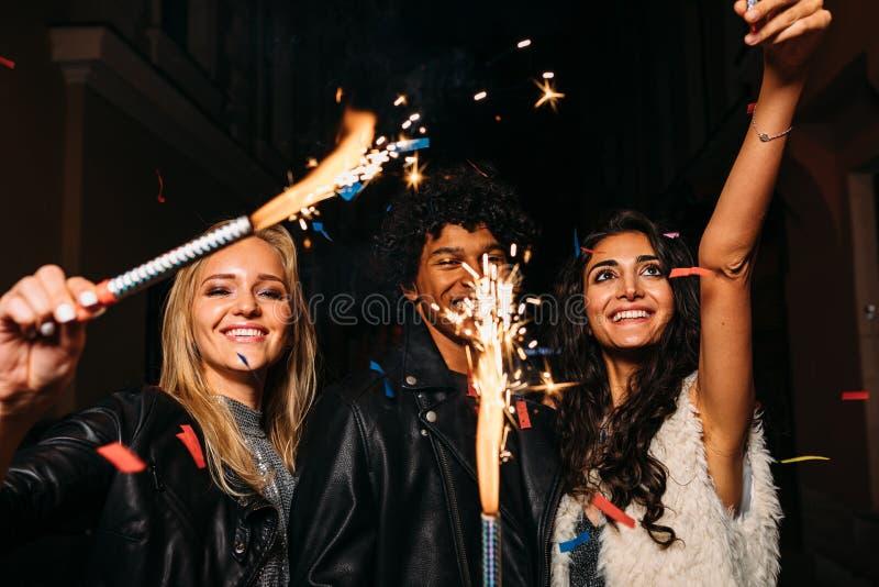 Gente joven que se divierte con las bengalas al aire libre fotos de archivo libres de regalías