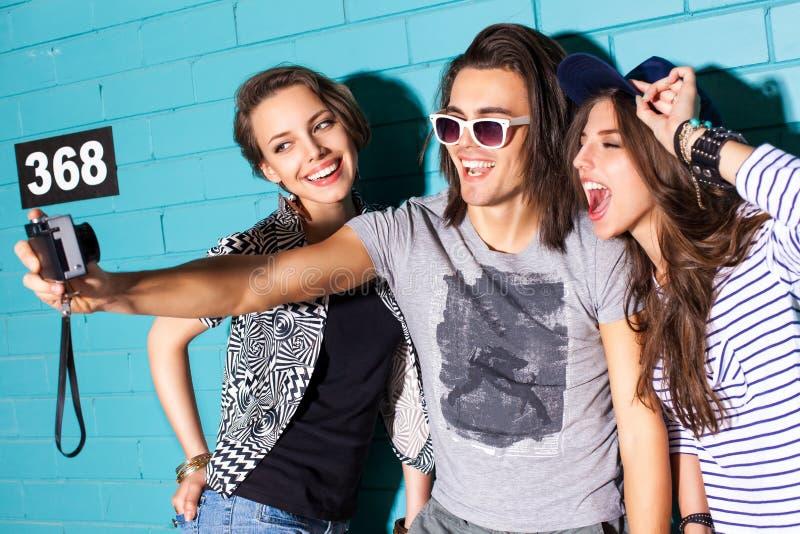 Gente joven que se divierte delante de la pared de ladrillo azul clara foto de archivo