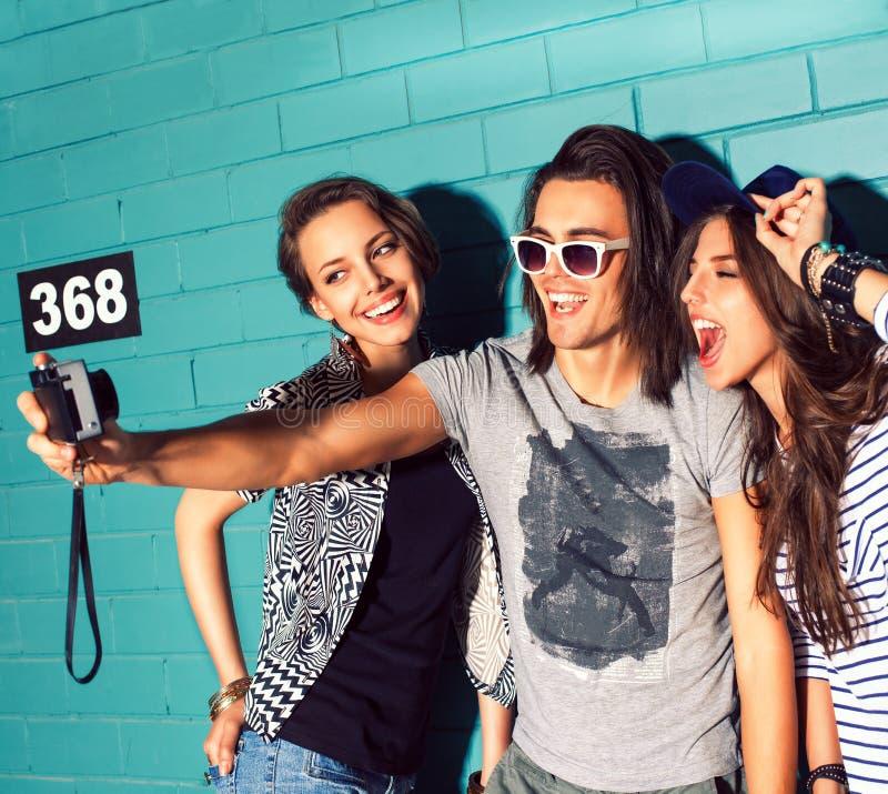 Gente joven que se divierte delante de la pared de ladrillo azul clara imágenes de archivo libres de regalías