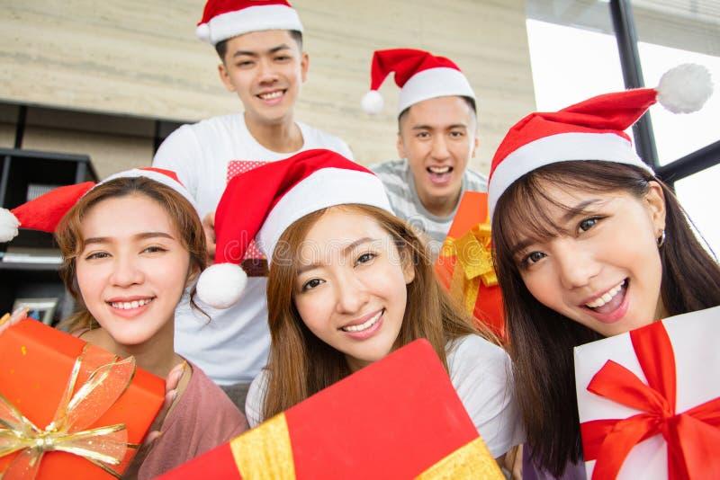 Gente joven que se divierte y que muestra el regalo de la Navidad imágenes de archivo libres de regalías