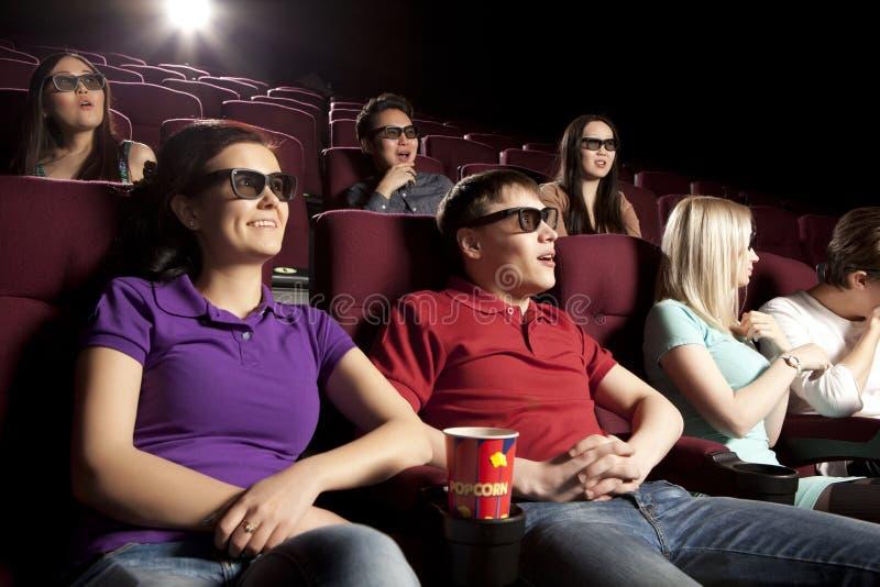 Gente joven que se sienta en el cine, mirando una película y comiendo p imagen de archivo