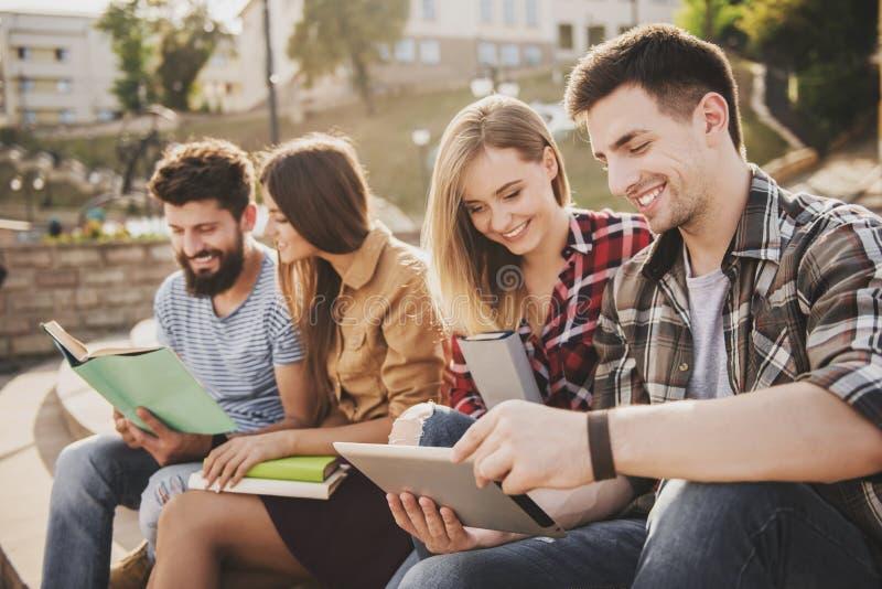 Gente joven que se sienta en parque y libros leídos foto de archivo libre de regalías