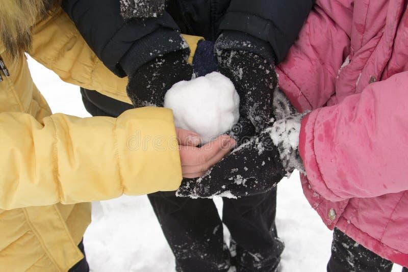 Gente joven que sostiene una bola de nieve en sus manos en el parque del invierno fotos de archivo