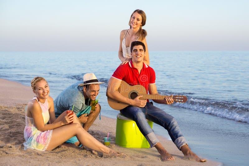Gente joven que tiene sus vacaciones en la playa imágenes de archivo libres de regalías