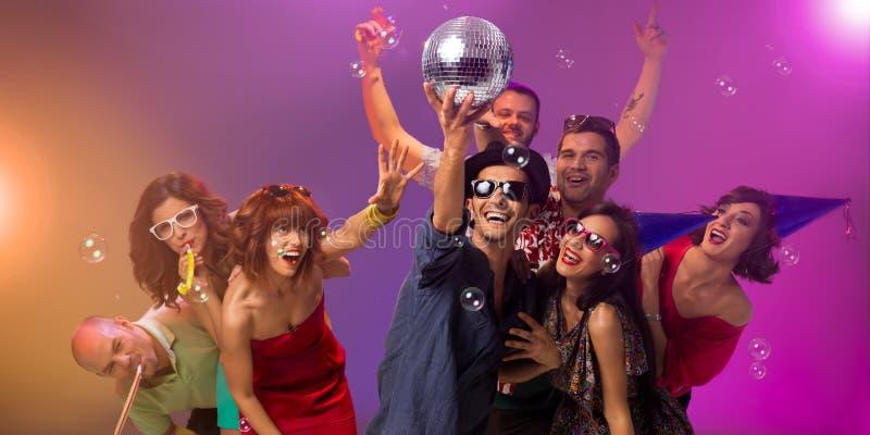 Gente joven que va de fiesta con la bola de discoteca foto de archivo libre de regalías