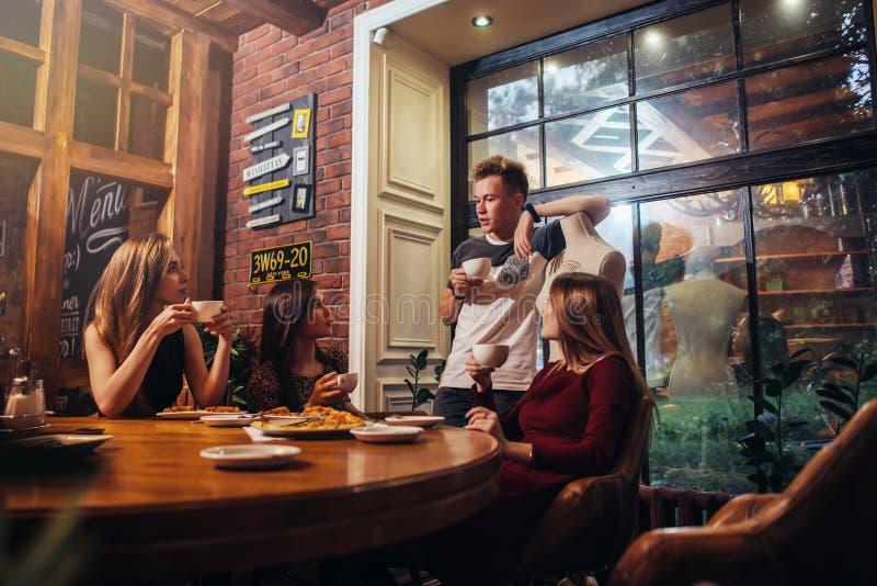 Gente joven seria que se sienta en una discusión de consumición del té del café de moda imagen de archivo libre de regalías