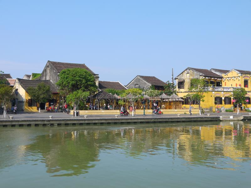 Gente local, barcos, casas amarillas por el río, y turistas en la ciudad antigua de Hoi An foto de archivo libre de regalías