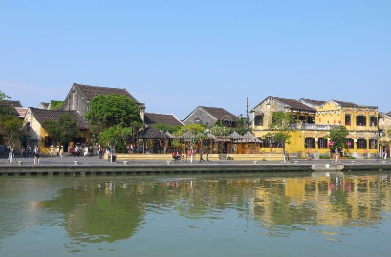 Gente local, barcos, casas amarillas por el río, y turistas en la ciudad antigua de Hoi An foto de archivo