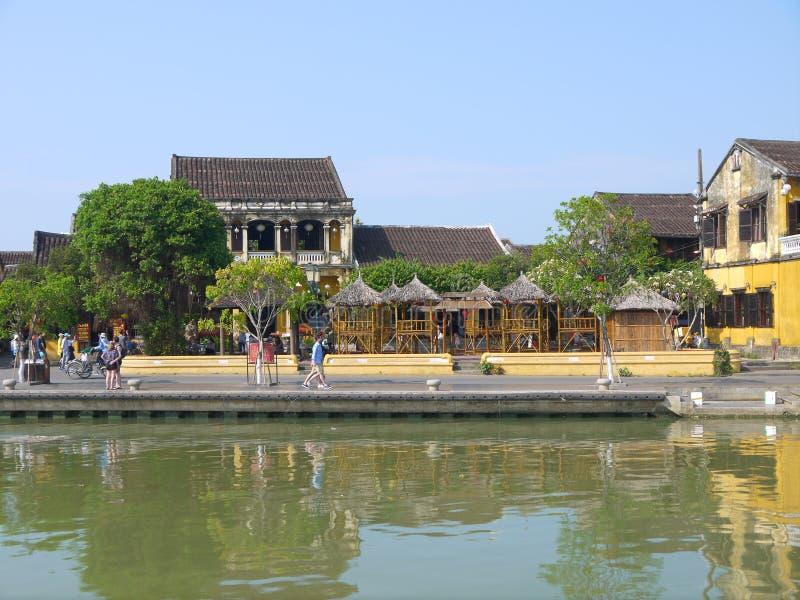Gente local, barcos, casas amarillas por el río, y turistas en la ciudad antigua de Hoi An imágenes de archivo libres de regalías