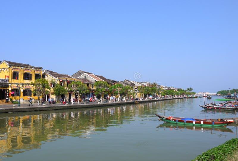 Gente local, barcos, casas amarillas por el río, y turistas en la ciudad antigua de Hoi An fotos de archivo libres de regalías