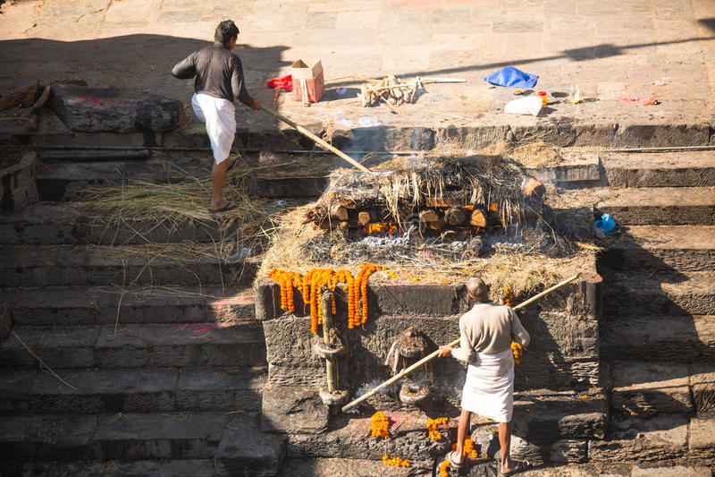 Gente local durante la ceremonia de la cremación a lo largo del río santo de Bagmati en Bhasmeshvar Ghat en el templo de Pashupat foto de archivo