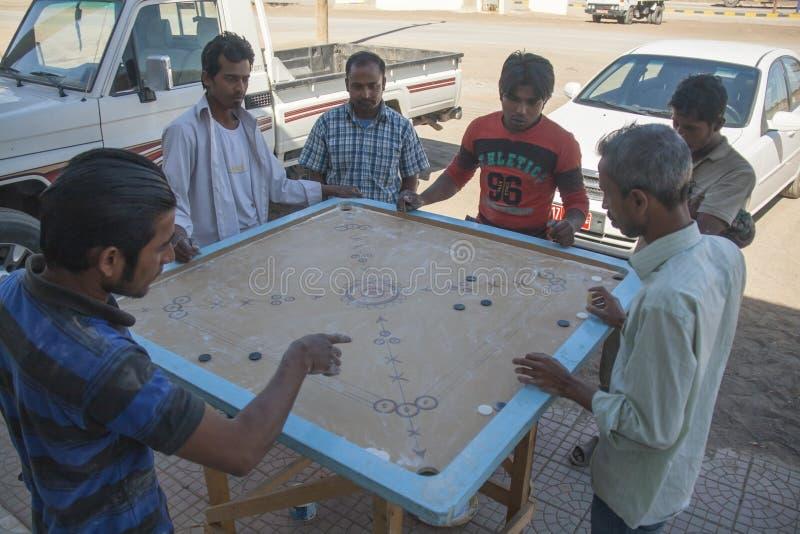 Gente local que juega al juego de Carrom, o Karrom, en la ciudad de Al Wassi, Omán fotos de archivo