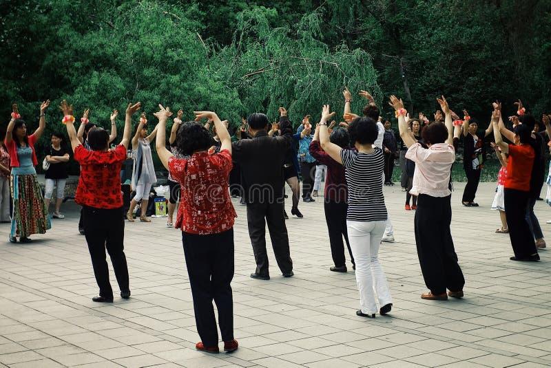 gente local que tiene un ejercicio de la ji del tai de la danza en un jardín del parque público imagenes de archivo