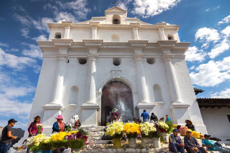 Gente locale che vende giorno giallo Guatemala di Roman Catholic Church Chichicastenango Market dei fiori immagine stock