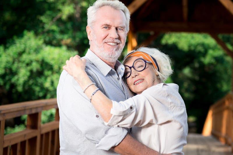 Gente mayor emocional que sonríe mientras que abraza en el puente fotos de archivo