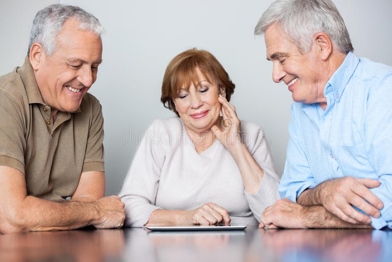 Gente mayor feliz que mira la tableta de Digitaces en clase del ordenador fotografía de archivo libre de regalías