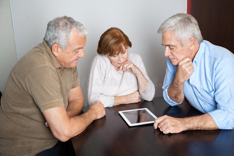Gente mayor pensativa que usa la tableta de Digitaces en clase del ordenador fotografía de archivo libre de regalías