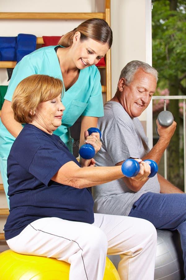 Gente mayor que hace pesa de gimnasia foto de archivo libre de regalías