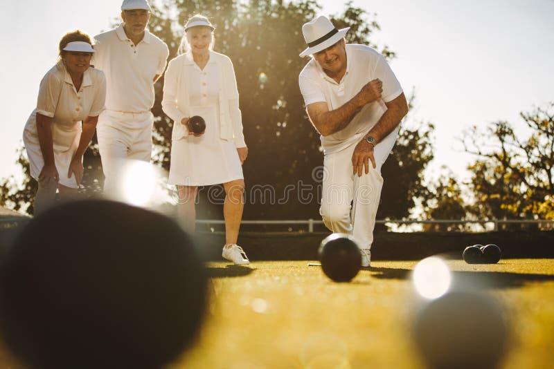 Gente mayor que juega boules en un parque foto de archivo