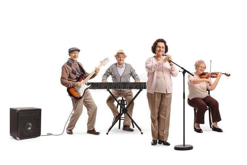 Gente mayor que juega en la guitarra, el violín y el teclado en una banda musical fotos de archivo