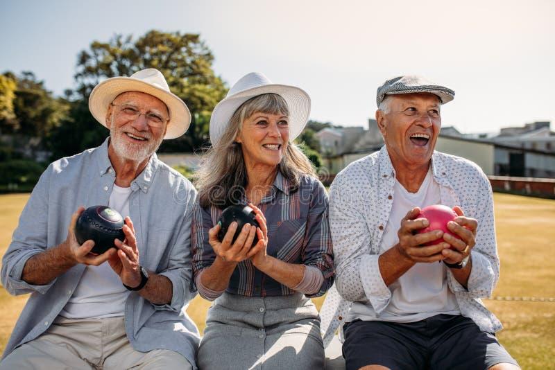 Gente mayor que se sienta junto en un banco en un parque que lleva a cabo el boul fotografía de archivo libre de regalías