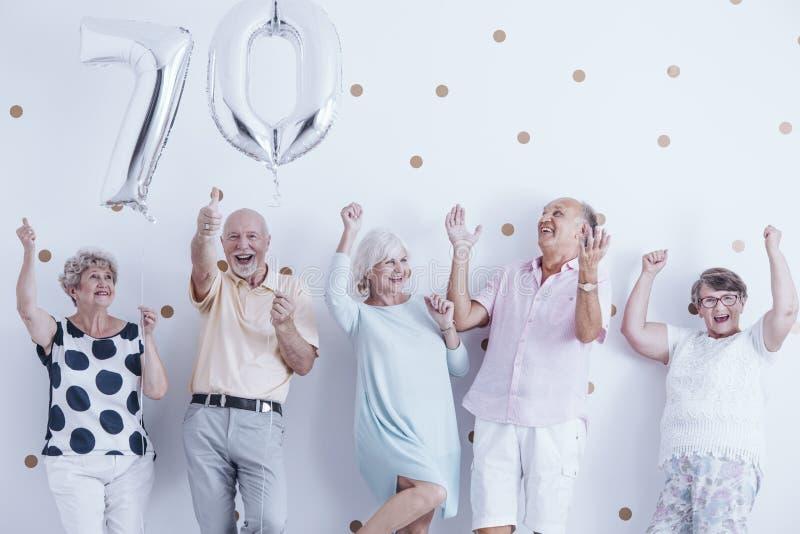 Gente mayor sonriente que celebra con los globos de plata fotos de archivo libres de regalías
